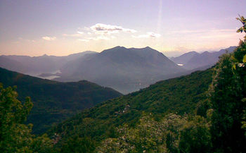 Blick von einer der obersten Kehren Richtung Westen über den Lago di Como. Rechts ist noch ein Zipfel des Lago di Lugano zu erkennen, darüber sind ganz schwach in der Ferne die 4000er des Monte Rosa-Gebiets zu erahnen.