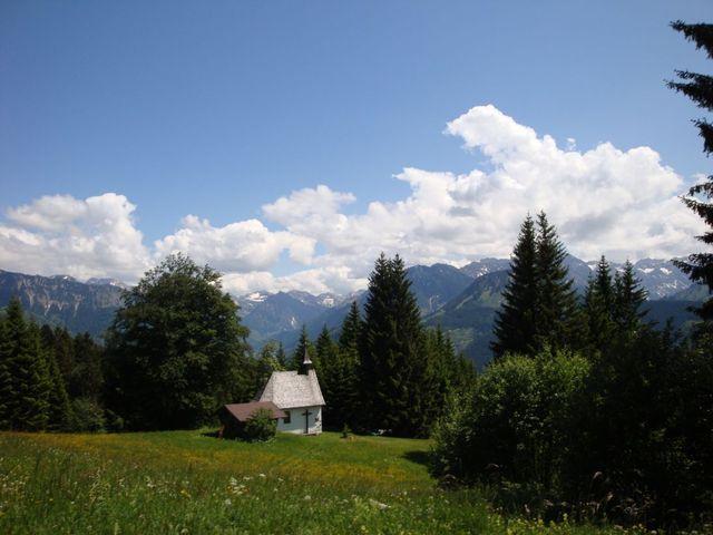 Das Allgäu von seiner schönsten Seite:die kleine Kapelle dürfte das Bildstöckle sein, das dem Anstieg seinen Namen gibt - denn einen Berg mit diesem Namen gibt es hier nicht. Im Hintergrund rechts die Berge der Daumengruppe, weiter links die Bergkette, die die Grenze zu Österreich bildet mit Gaishorn und Rauhhorn.