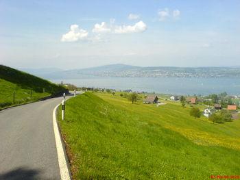 Sicht auf Luegete (weisses Haus über der Strasse), im Hintergrund in der Mitte über dem Zürichsee mein Hausberg, der Pfannenstiel, 800 m ü. M., ganz hinten links im Dunst der Zürcher Hausberg (Wanderer und Dickpneu-Fahrer), der Üetliberg, 870 m ü. M.