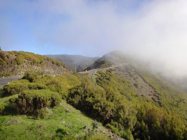 Blick aus Richtung Alto da Fonte do Bispo. Von rechts kommt die ER211 von Calheta, in den Wolken liegt der Parkplatz Rabaçal.